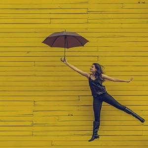 A woman using an umbrella to fly in front of a yellow wall.