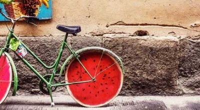 A green bicycle with wheels that look like slices of watermelon.