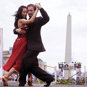 A couple dancing the tango with the Buenos Aires monument in the background.