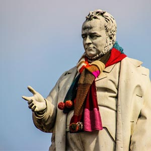A statue wearing a bright, knitted scarf.
