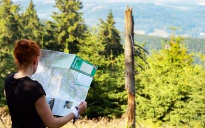 a young woman in nature reading a map.