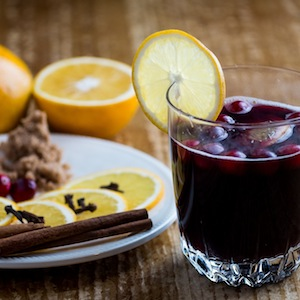 A glass of mulled wine with a slice of lemon and spices.