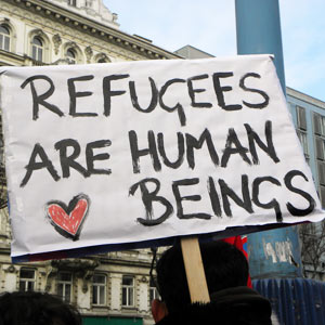 A protest sign reading refugees are human beings.