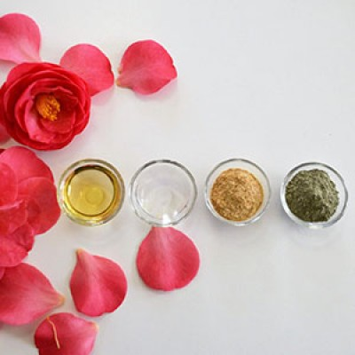 Flower petals and four glass bowls of organic skincare ingredients on a table.