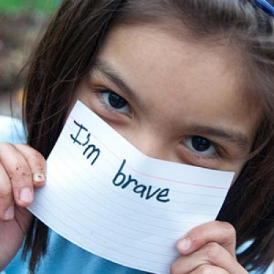 A girl smiles and holds a sign saying I'm brave.
