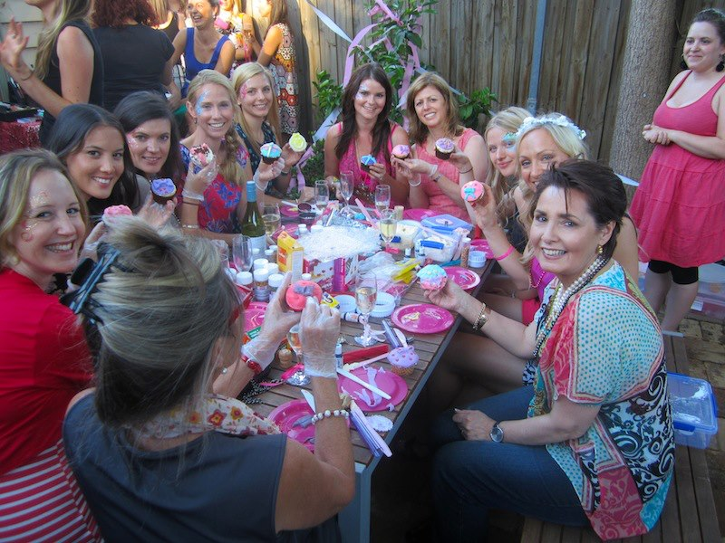 A hens' party decorating cupcakes in a garden party setting.