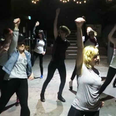 A class performing the dance routine to Micheal Jackson's Beat It.