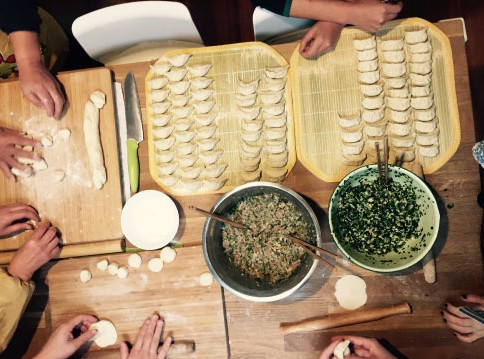 People at a dumpling making class and a tray of dumplings.