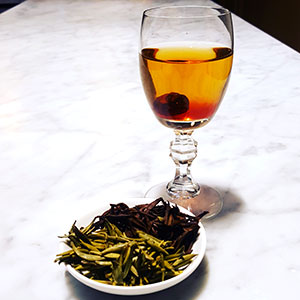 A glass of cold brewed tea and tea leaves.