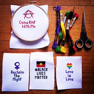 Cross stitch messages advocating for different activist causes.