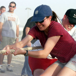 A woman laughs while playing in a tug-of-war team building game.