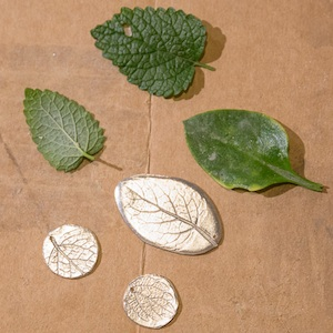 Silver pendants with leaf patterns embossed in them.