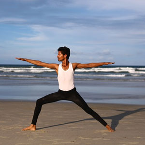 A man in a yoga pose on a beach.