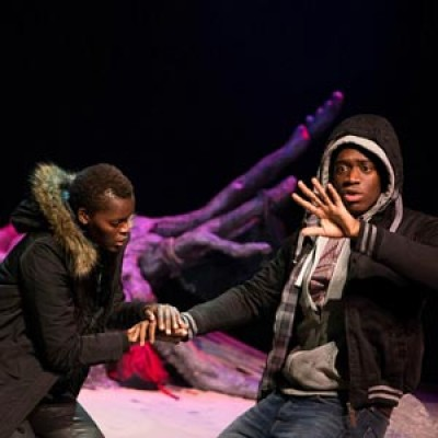 Two actors perform on a theatre stage.