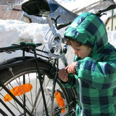 A young child playing at bicycle maintenance.