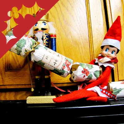 A nut-cracker and elf pull a Christmas cracker.