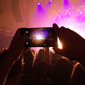 Filming a concert with a mobile phone.