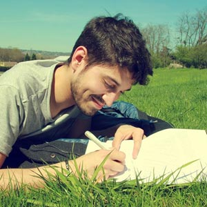 A man writing in a journal and smiling
