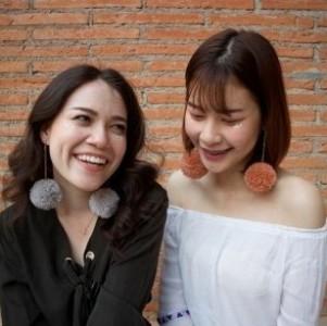 two women wearing pom pom earrings