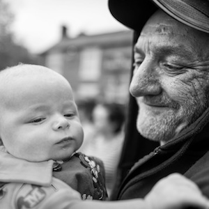 old man holding baby